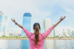 Back shot of young asian woman relax herself and warm down after city running exercise with a city view background. Stock Photography