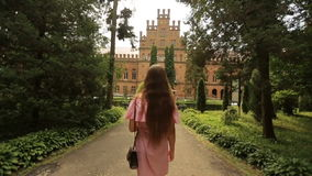 Back shot of young woman on allley in old park around the ancient university buildings.  stock video footage