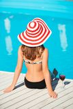 Back shot of young woman sitting close by swimming. Back shot of beautiful young woman sitting close by swimming pool with wine glass at hot summer day Royalty Free Stock Photos