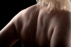 Back shoulder blond woman in low key royalty free stock image