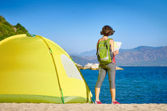 Back side of backpacker girl searching right direction on map. Stock Photo