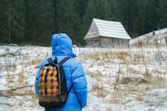 Back side of backpacker man walking to old Royalty Free Stock Images