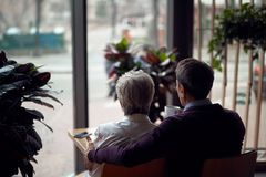 Back side beloved aged couple sitting in cafe. Enjoyable meetings. Back side portrait of happy aged men and women embracing while sitting together in cafe and royalty free stock photography