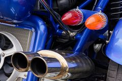 Back side of a blue motorcycle. Lovely detail shot of lights and shiny exhaust pipes Royalty Free Stock Photos
