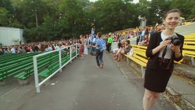Back side of cheering people at summer live concert. Music band performing on stage. Crowd. Jumping stock video