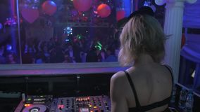 Back side of Dj girl in mouse ears spinning at turntable in club. MC on stage stock video