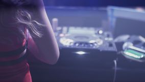 Back side dj girl in red dress spinning at turntable in nightclub. Dancing. Headphones. Illuminations stock video