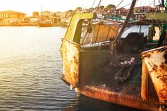 The back side of a fishing trawler. The back side of a fishing an old trawler moored in a harbor with the glow of the sun in the corner royalty free stock photo