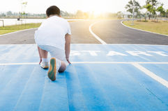 Back side of fit and confident fat boy in starting position. Ready for running. kid athlete about to start a sprint with bright sunlight Royalty Free Stock Photos