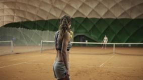 Back side footage of a pretty, young woman with leg prosthesis playing tennis with the rival. Ball serving. Slow motion.  stock video footage