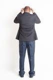 Back side full length mature Indian businessman thinking Stock Photo