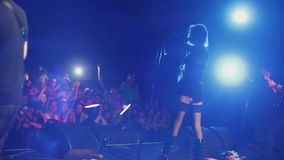 Back side of girl in black mini dress, rock shoes perform on stage of nightclub. Illuminations stock video