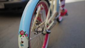 Back side of girl cycling in summer day wheel of a bicycle focus in. Slow motion