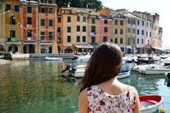 Back side of girl looking at Portofino harbour and colorful houses, Italy, italian travel concept. royalty free stock photography