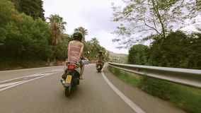 Back side of girls ride on scooters on road between green hills. Palm trees. Traveling. Journey stock footage