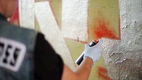 Back side graffiti artist paint spraying the wall. Summer day. Vandalism. Back side graffiti artist paint spraying the wall. Summer day stock video