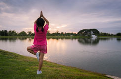Back side of little girl play yoga or exercise. On park with sunset, healthy concept Stock Photos