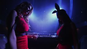 Back side mc girl and dj girl in hare mask dance at turntable in nightclub. Clap. Blue spotlights stock footage