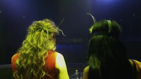 Back side of mc girl and Dj girl in hare masks perform at turntable in nightclub stock video