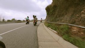 Back side people in helmets ride on motorcycle on road at mountains full of green trees. Traveling. stock video