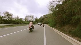 Back side people in helmets ride on motorcycles on road between hills full of green trees. Traveling stock video