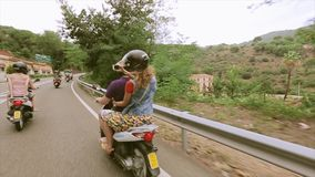 Back side of people in helmets ride on scooters on road. Hills. Green trees. Traveling. Journey stock video footage