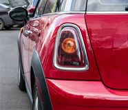 The back and side of a red Mini Cooper. One back headlight of a red Mini Cooper parked on the street. stock photo