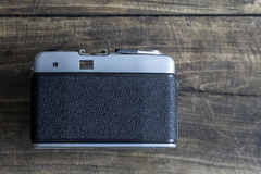 Back side of retro camera. On wooden background, from above Royalty Free Stock Photos