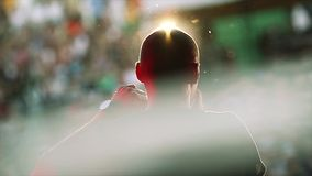 Back side of silhouette man in sun beams play on harmonica at microphone on stage. Live concert. stock footage