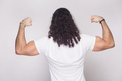 Back side of strong bodybuilder man in white t-shirt with long w stock photos