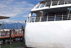 Back side of the touristic ferry boat. Close up  of touristic ferry boat in harbour with mountains on background Royalty Free Stock Photo