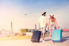 Young couple traveling with luggage. Back side of traveler couple, freedom and active lifestyle concept royalty free stock images