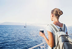 Back side of traveler girl looking at the sea, travel and active lifestyle concept. Beautiful young woman with a cup of coffee looking at the sea Royalty Free Stock Photos