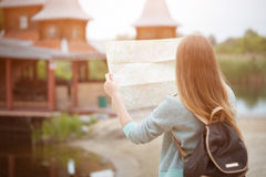 Back side of traveler girl searching right direction on map, orange sunset light, traveling along Europe Royalty Free Stock Images