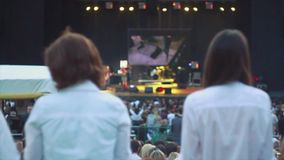 Back side of two girls in blue shirts at summer live concert. Music band performing on stage. Crowd. Spotlights. Slow motion stock video footage