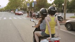 Back side of two girls in helmets drive on scooter in city. Summer evening. Green trees. Cold shades. Back side of two young girls in helmets drive on scooter in stock footage
