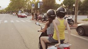 Back side of two girls in helmets drive on scooter in city. Summer evening. Green trees. Warm shades. Back side of two young girls in helmets drive on scooter in stock video footage