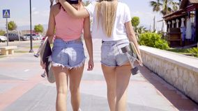 Back side of two girls with skateboards. Back side of two girls in short jeans and backward hats walking with skateboards on sidewalk stock footage