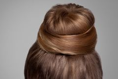 Back side view closeup portrait with creative elegant brown collected hairstyle, bun hair. Indoor studio shot, on grey background royalty free stock photos