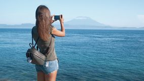 Back side view of girl traveler with backpack takes photo of ocean and volcano on phone stock footage