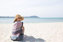 Back side view of the happy young woman in straw hat siting and relaxing on the beach stock photo