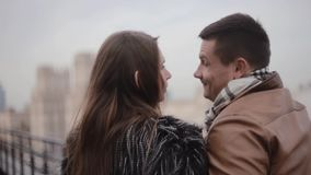 Back and side view of lovers on a roof enjoying the city view. They kiss, talk smile to each other. Cold foggy weather. Back and side view of happy lovers on a stock video