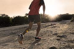 Sport man with ripped athletic and muscular legs running uphill off road in jogging training workout royalty free stock photography