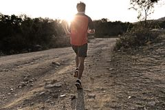 Sport man with ripped athletic and muscular legs running uphill off road in jogging training workout royalty free stock images