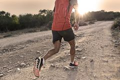 Sport man with ripped athletic and muscular legs running uphill off road in jogging training workout stock photos