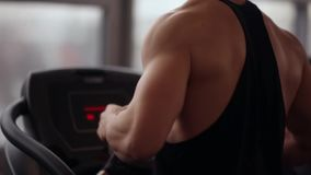 Back and side view of a strong bodybuilder running on a treadmill while working out in a sport club. Healthy lifestyle. stock video footage