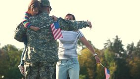 Back side view USA soldier in camoubackgrounde hugging with family. Embracing wife and daughter on the summer lawn stock video