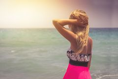 A back side view on a wonderful young woman watching to sea and raising her hands on sunrise.  stock photography