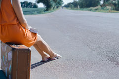 Back side view of young pretty woman hitchhiking waiting along the road for a ride Stock Image