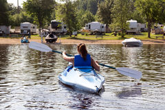 Back side of a woman kayaking on a calm lake. Woman kayaking alone at Maskinonge Lake at summer time in front of the beach royalty free stock image